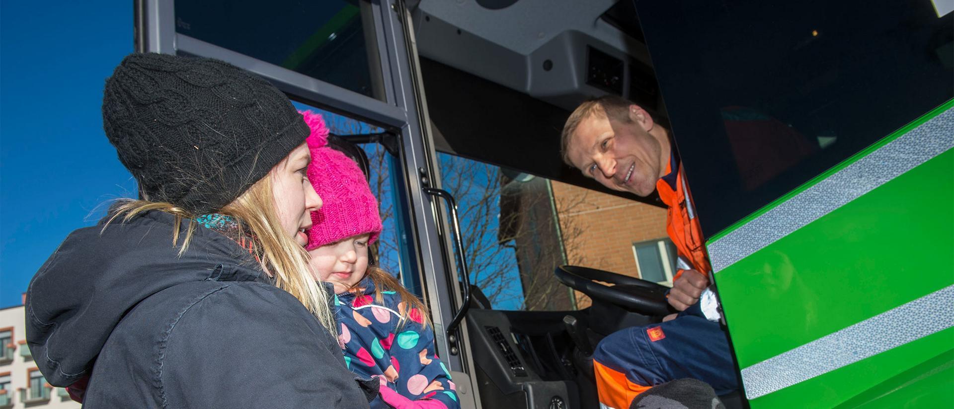 Jäteauton kuljettaja juttelee naisen ja lapsen kanssa