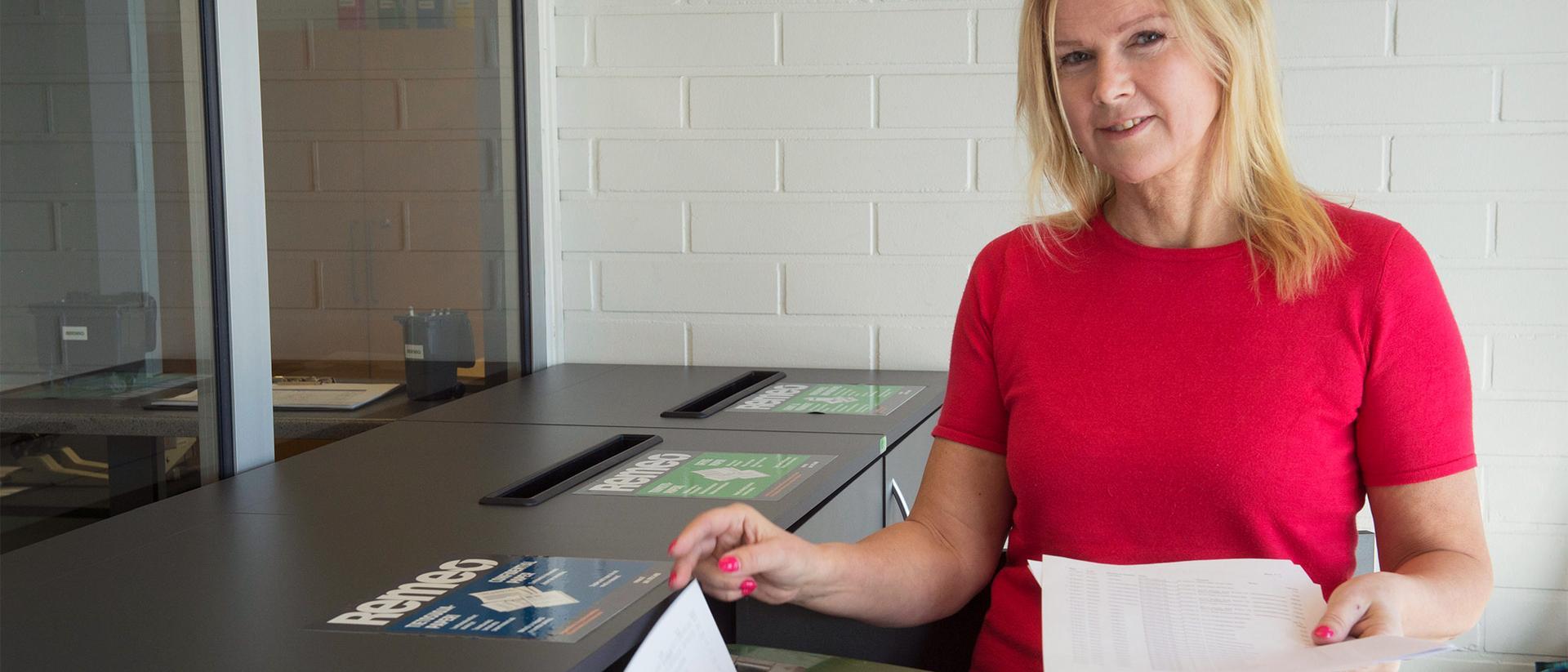 Nainen laittaa paperia tietoturva-astiaan