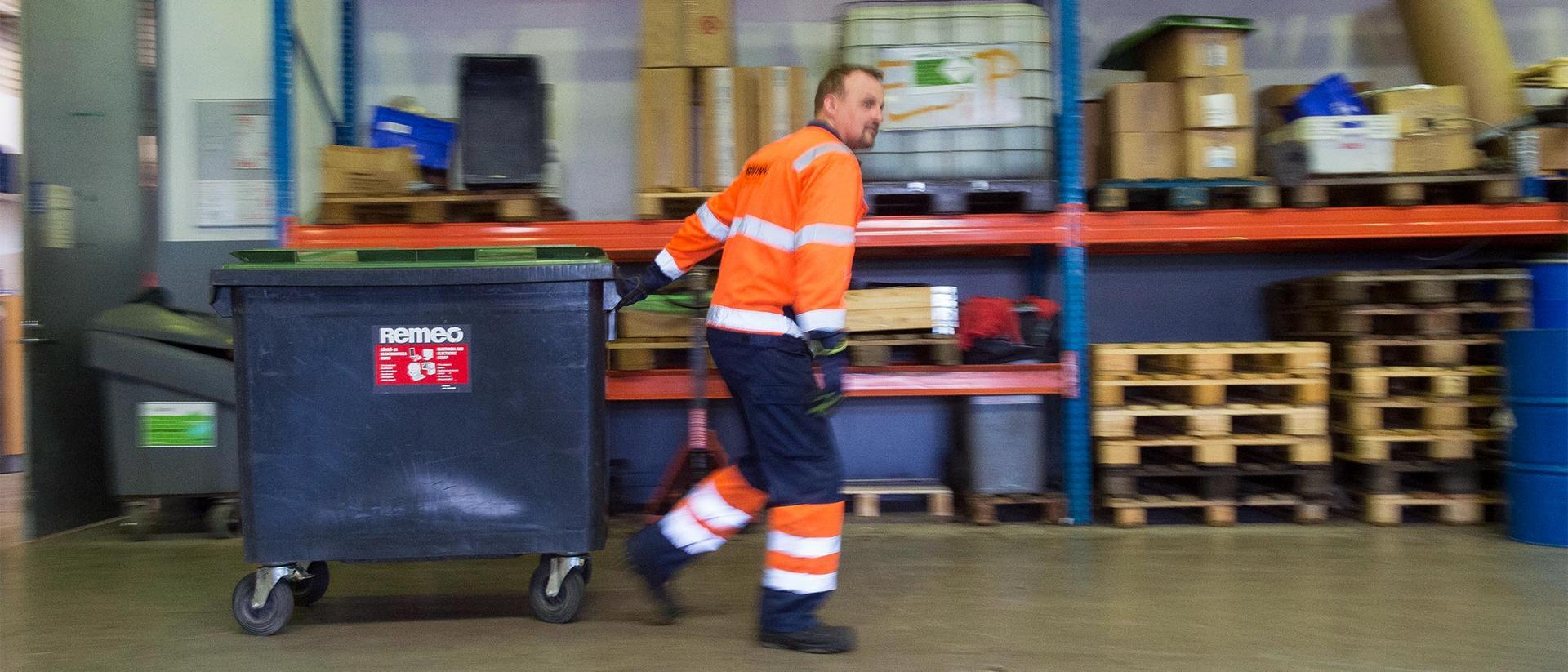 Työntekijä noutamassa vaarallisia jätteitä